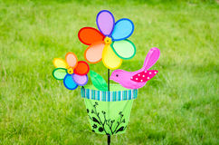 Colorful double pinwheel with bird on green grass Stock Photography