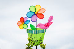Colorful double pinwheel with bird on white sky Royalty Free Stock Image