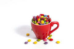 Colorful dragees in red cup royalty free stock images