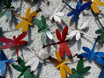 Colorful dragonflies made out of paint cans. On white wall stock images