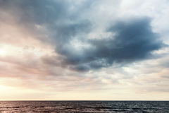 Colorful dramatic sky with clouds over sea water. At sunrise Royalty Free Stock Photography