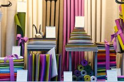 The colorful drapery shop window with fabric rolls and stacks of different shapes and colors royalty free stock photography