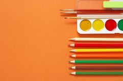 Colorful drawing items set on orange. Colorful pencils and watercolors as border on textured orange paper as background. Top view, flat lay royalty free stock photo