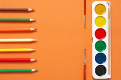 Colorful drawing items set on orange. Colorful pencils and watercolors as frame on textured orange paper as background. Top view, flat lay royalty free stock images