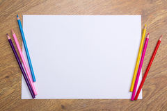 Colorful drawing pencils and blank paper on wooden table. Background royalty free stock photo