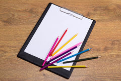 Colorful drawing pencils and clipboard with blank paper on woode Royalty Free Stock Photography