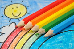 Colorful drawing: smiling sun, rainbow, blue sky Royalty Free Stock Images
