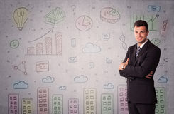 Colorful drawings on wall with businessman. A young adult businessman standing in front of a wall with colorful drawings of buildings, charts, graphs, signs Stock Image