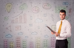 Colorful drawings on wall with businessman. A young adult businessman standing in front of a wall with colorful drawings of buildings, charts, graphs, signs Stock Photo