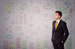 Colorful drawings on wall with businessman. A young adult businessman standing in front of a wall with colorful drawings of buildings, charts, graphs, signs Stock Photography