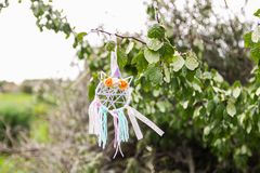 Colorful dreamcatcher on summer nature background. Handmade decor made of feathers, ribbons, threads and beads. Colorful dreamcatcher outdoors on summer nature royalty free stock photos