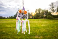 Colorful dreamcatcher on summer nature background. Handmade decor made of feathers, ribbons, threads and beads. Colorful dreamcatcher outdoors on summer nature stock photo