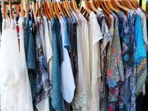 Colorful Dresses on Hangers. A large number of colourful summer dresses on hangers at outside market stall royalty free stock images