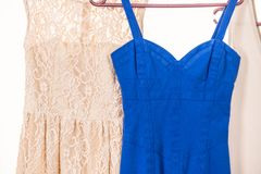 Colorful dresses hanging on clothes hanger. Many colorful dresses, blue and creamy hanging on clothes hanger in wardrobe, white background stock photo