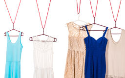 Colorful dresses hanging on clothes hanger. Many colorful dresses, blue and creamy hanging on clothes hanger in wardrobe, white background royalty free stock photography