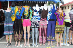 Colorful dresses and pants on mannequins at an outdoor flea market. Colorful print dresses, slacks, and African dashikis on mannequins at an outdoor flea market stock photography