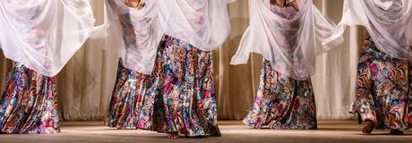 Colorful dresses and white scarves on stage. Dancers visible to the waist, with gorgeous, colorful dresses and white scarves on stage stock images