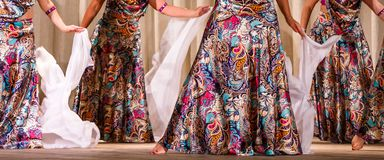 Colorful dresses and white scarves on stage. Dancers visible to the waist, with gorgeous, colorful dresses and white scarves on stage royalty free stock images