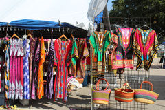 Colorful dresses and woven bags at an outdoor flea market. Colorful print dresses, woven bags, and African dashikis hanging on racks at an outdoor flea market stock photography