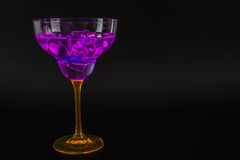 Colorful drink in a cocktail glass, with ice cubes, summer drink Stock Photography