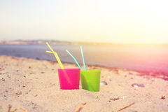 Colorful drink cups in the sand Royalty Free Stock Photo