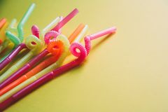 Colorful drinking straws against yellow background royalty free stock photography