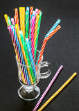 Colorful drinking straws in the glass on black background Royalty Free Stock Image