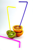 Straws in ripe orange and kiwi fruit Royalty Free Stock Photos