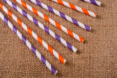 Colorful drinking striped straws on the background of burlap Royalty Free Stock Image