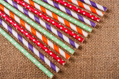 Colorful drinking striped straws on the background of burlap Stock Image