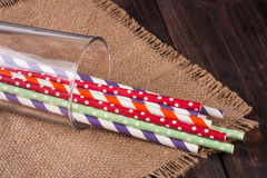 Colorful drinking striped straws in glass on a wooden table with sacking Stock Images