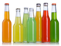 Colorful drinks in bottles. Row of different colored drinks in glass bottles, isolated on white background royalty free stock photos
