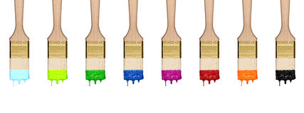Colorful dropping set of paint brushes in a row. Isolated on white background stock photo