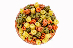 Colorful dry pasta in wooden bowl. Colorful dry pasta with spinach and tomatoes in wooden bowl Royalty Free Stock Photo