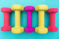 Colorful Dumbbells on Yoga Mat. Five colorful dumbbells arranged symmetrically on a blue yoga mat Royalty Free Stock Images