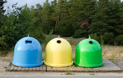 Colorful dustbins. Dustbins of blue, yellow, green colors with nature background Stock Photos