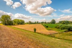 Colorful Dutch landscape with fascinatingly beautiful clouds. Picturesque composition of different colored fields seen from a Dutch on a sunny day with special royalty free stock image