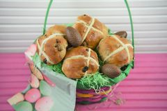 Chocolate Easter eggs and food in a gift basket with pink table background stock photos