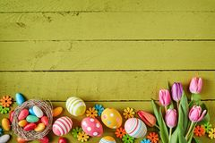 Colorful Easter border on green wood. With fresh spring tulips, decorative eggs, candy in a nest and small floral decorations with copy space Royalty Free Stock Photography
