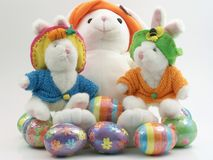 Colorful Easter bunnys with eggs. Mother easter bunny with her two kids plus eggs Royalty Free Stock Photo