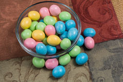 Colorful Easter candy in a bowl. Candy coated Easter eggs in a glass bowl on a tapestry Royalty Free Stock Image