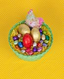 Colorful Easter chocolate eggs in a green basket Royalty Free Stock Image