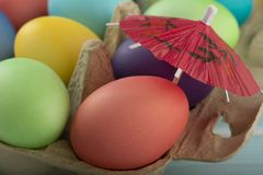 Colorful Easter eggs under umbrella in a box royalty free stock photo
