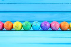 Colorful easter egg on blue pastel color wood background with space.  Royalty Free Stock Image