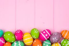 Colorful Easter egg bottom border against pink wood Stock Image