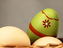 Colorful Easter egg in the company of ordinary eggs. Royalty Free Stock Images