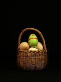 Colorful Easter egg in the company of ordinary eggs. Royalty Free Stock Image