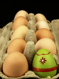 Colorful Easter egg in the company of ordinary eggs. Stock Photo