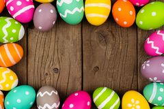 Colorful Easter egg frame against a rustic wood background Stock Photo