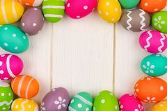 Colorful Easter egg frame against a white wood background Royalty Free Stock Photos